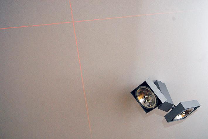 Pionowe linie wyświetlane przez poziomicę Bosch GLL 3-50 przecinają się na suficie pod kątem 90 stopni